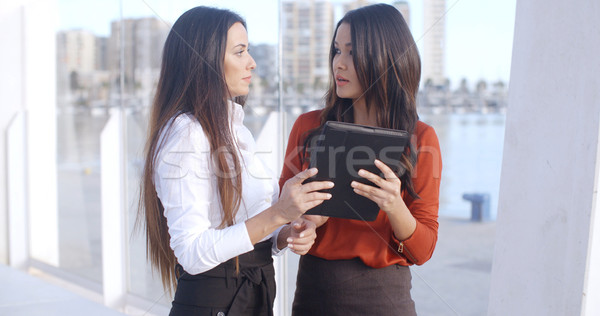 Two women laughing at a tablet computer Stock photo © dash