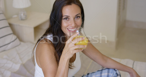 Smiling healthy young woman drinking orange juice Stock photo © dash