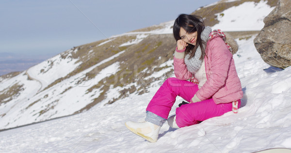 Smiling woman sat on snowy mountain summit Stock photo © dash