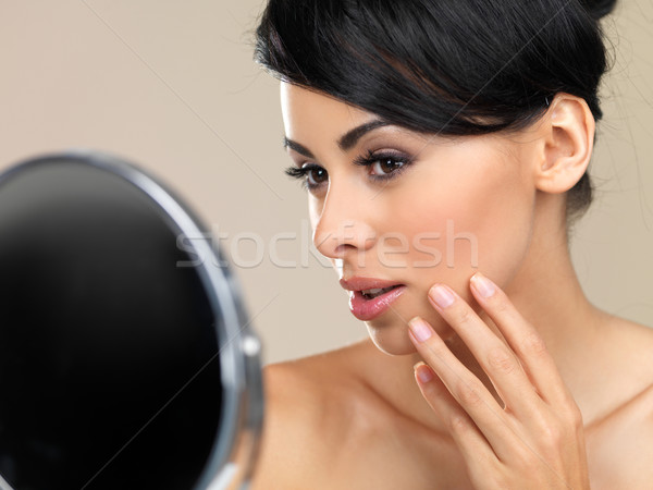 Beautiful woman looking in a hand mirror Stock photo © dash