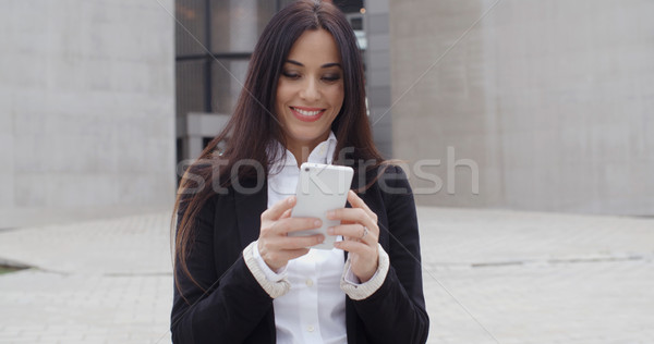 Attractive businesswoman checking her mobile phone Stock photo © dash