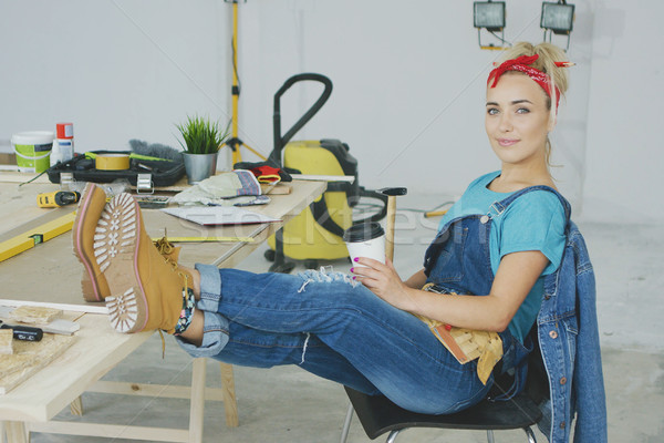 Female relaxing at carpenter workbench with drink  Stock photo © dash