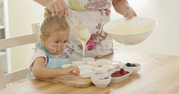 Parent pouring muffin batter into holders Stock photo © dash