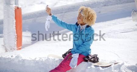 Woman sitting on snowbank texting Stock photo © dash