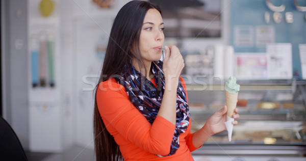 Smiling young woman savoring an ice cream cone Stock photo © dash