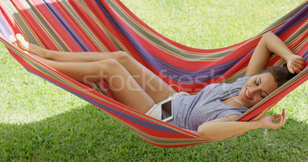 Happy young woman relaxing in a colorful hammock Stock photo © dash