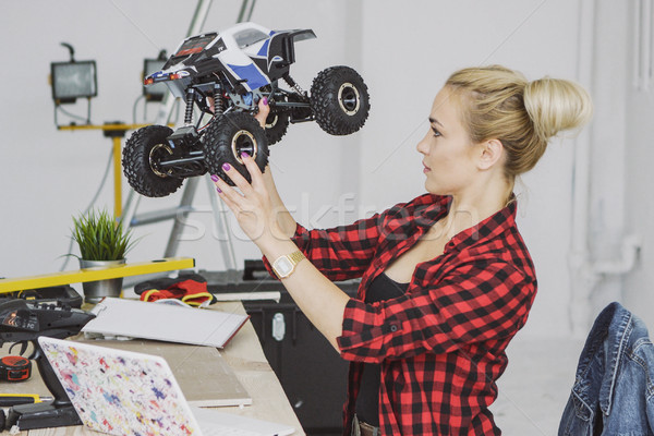 Woman examining radio-controlled car in workshop Stock photo © dash