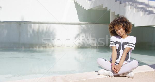 Női ül lábak keresztbe mosolyog visel póló Stock fotó © dash