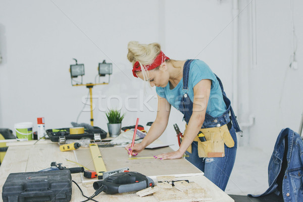 Female carpenter drawing lines on plywood sheet  Stock photo © dash