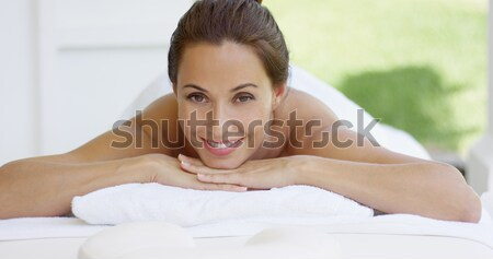 Woman with chin on folded towel smiles Stock photo © dash