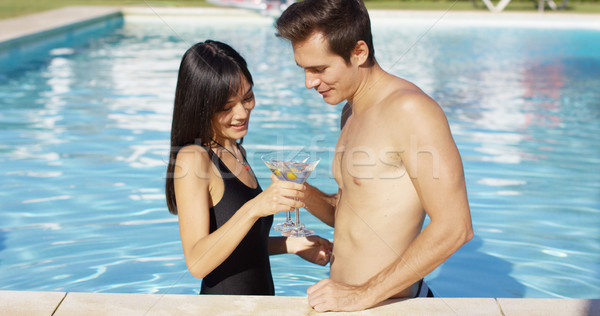 Cute mixed couple holding martini glasses in pool Stock photo © dash