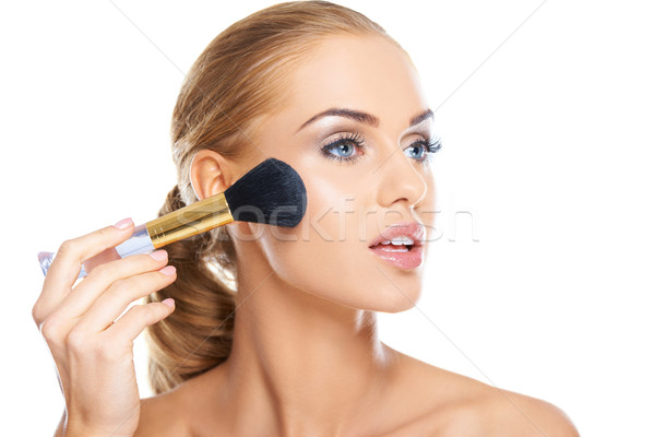 Beautiful woman applying blusher Stock photo © dash
