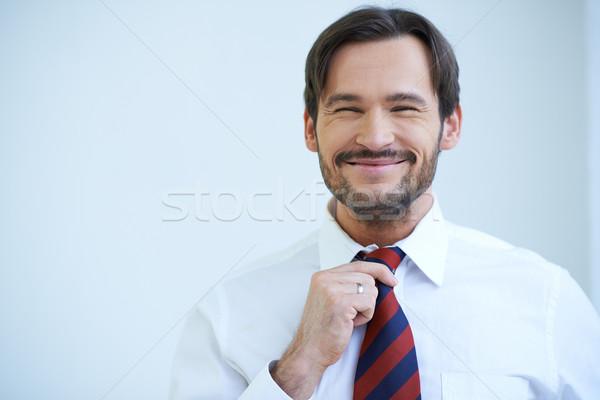 Happy bearded man straightening his tie Stock photo © dash