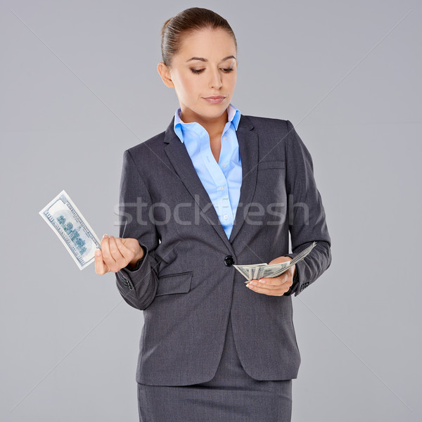 Stylish businesswoman holding dollar bills Stock photo © dash