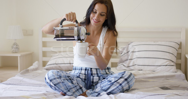 Happy young woman pouring herself coffee Stock photo © dash