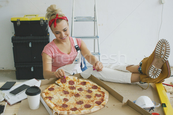 Woman in overalls eating pizza at workplace  Stock photo © dash