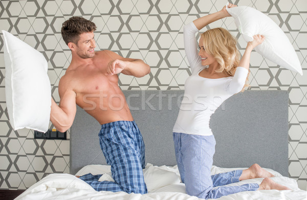 Playful couple having a pillow fight Stock photo © dash