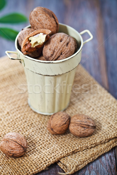 Walnuts with green leaves on the wooden background Stock photo © dashapetrenko