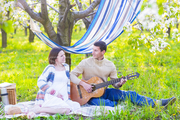 Pregnant couple in blooming garden at the picnic Stock photo © dashapetrenko