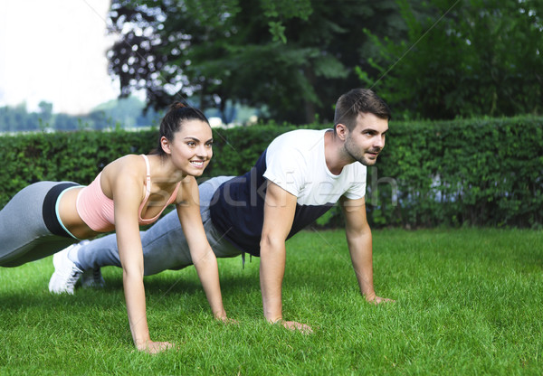 Young couple exercising and stretching muscles before sport acti Stock photo © dashapetrenko
