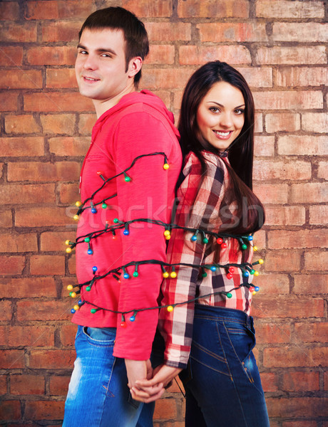 Happy young couple near brick wall with garland Stock photo © dashapetrenko
