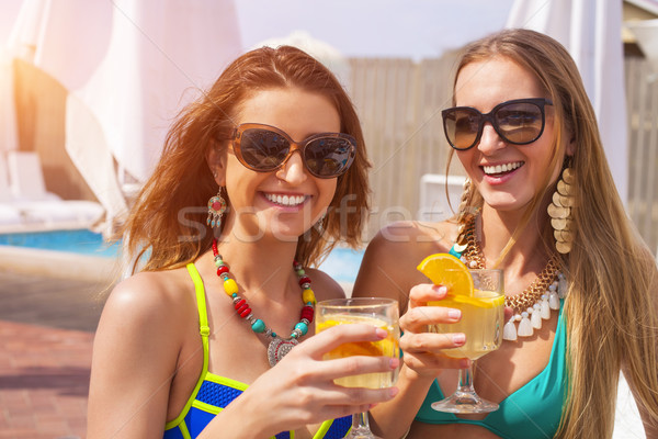 Happy girls with beverages on summer party near the pool Stock photo © dashapetrenko