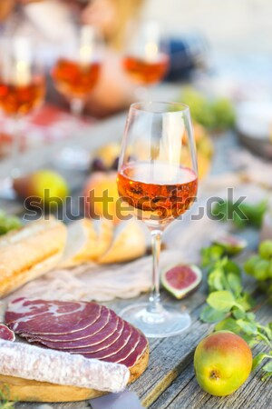 Stock photo: One glass of rose wine on table with fruits and cheese
