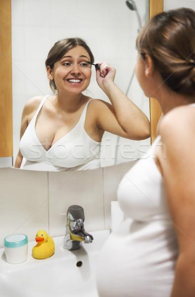 Jonge zwangere vrouw mascara naar spiegel Stockfoto © dashapetrenko