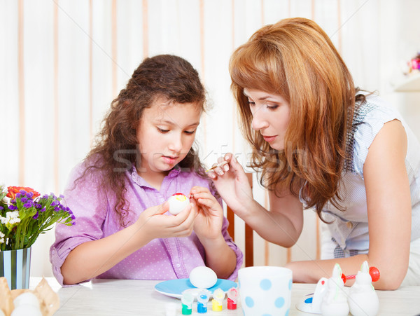 Mother and her little daughter painting on Easter eggs Stock photo © dashapetrenko