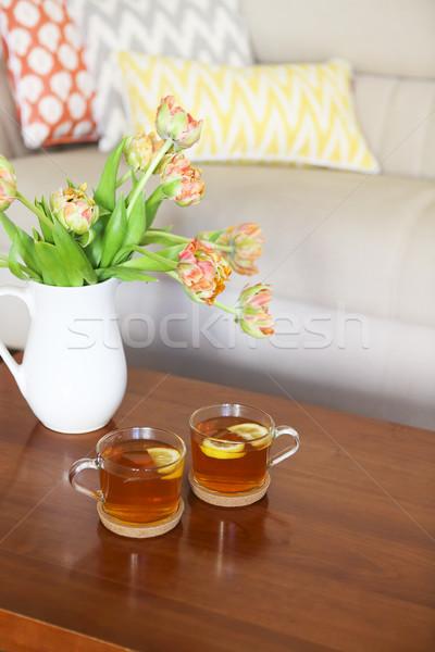 Beautiful orange tulips bouquet with two cups of tea  Stock photo © dashapetrenko