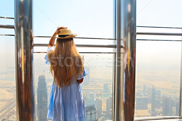 Girl tourist with mobile phone by the window of skyscraper of th Stock photo © dashapetrenko