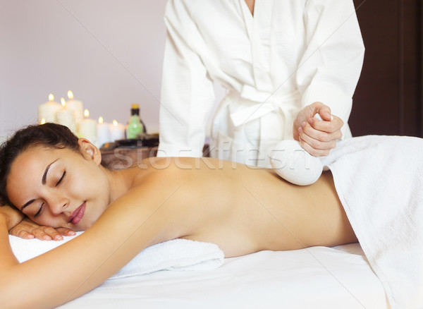 Beautiful young woman having back massage with pouch of rice Stock photo © dashapetrenko