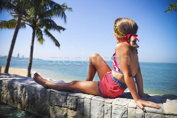 Little girl sitting underneath a palm at the tropical beach Stock photo © dashapetrenko