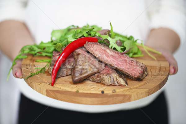 Sliced medium rare grilled Beef steak Ribeye in hands of a woman Stock photo © dashapetrenko