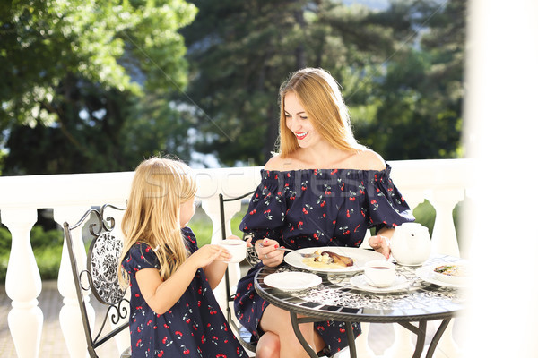 Cheerful mother and daughter sitting at outdoors cafe while drin Stock photo © dashapetrenko