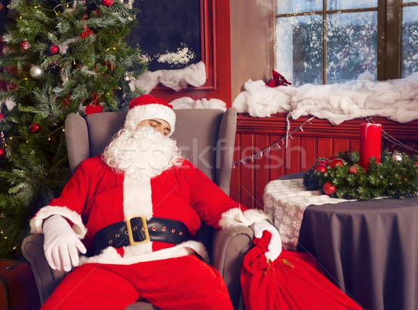 Photo of happy Santa Claus with big bag of presents sleeping  Stock photo © dashapetrenko