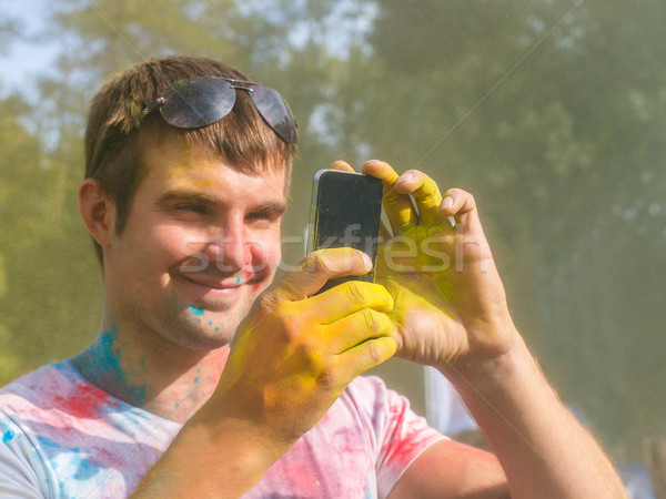 Man taking photo on mobile phone on holi color festival Stock photo © dashapetrenko