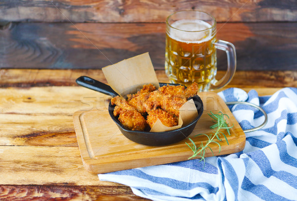 Beer and crispy fried chicken on a blue plaid towel on a wood ta Stock photo © dashapetrenko
