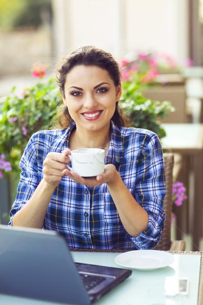 Young smiling woman woking on computer outdoors Stock photo © dashapetrenko