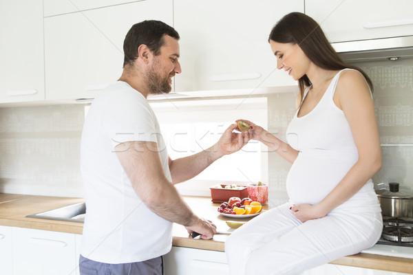 Pregnant woman and happy man in the kitchen Stock photo © dashapetrenko