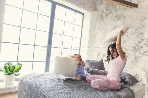 Family fun. Mother and daughter pillow fight Stock photo © dashapetrenko