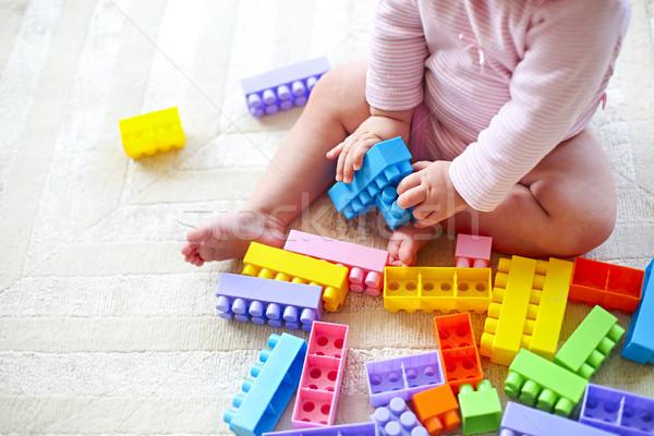 Cute toddler girl having fun with toy blocks sitting on the carp Stock photo © dashapetrenko