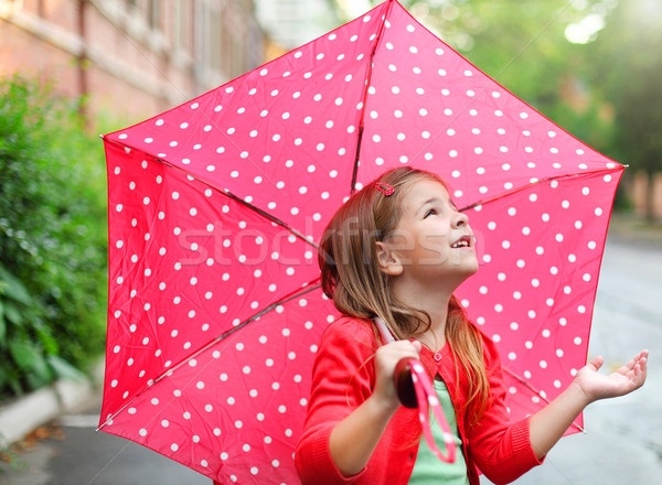 Little girl with polka dots umbrella under the rain Stock photo © dashapetrenko