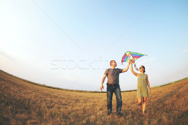 Happy young couple with flying a kite  Stock photo © dashapetrenko