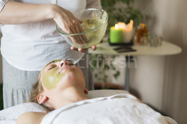 Beautiful relaxed woman having clay face mask in the spa salon  Stock photo © dashapetrenko