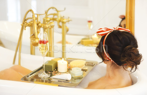 Attractive girl relaxing in bath on light background  Stock photo © dashapetrenko