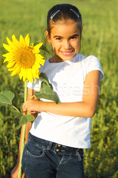 Stock photo: Portrait of a cute little girl with sunflower