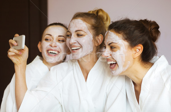 Three young happy women with face masks at spa resort. Frenship  Stock photo © dashapetrenko