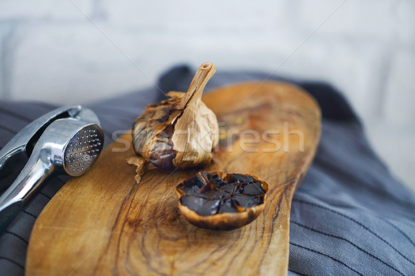 Black garlic bulbs and cloves on wooden background Stock photo © dashapetrenko