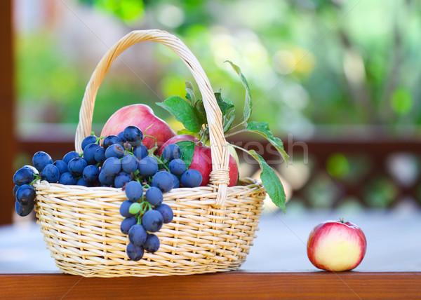 Tasty grapes and apples in the basket in the gazebo Stock photo © dashapetrenko